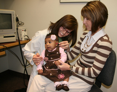 a baby girl, her mother, and an audiologist testing the girl's hearing